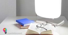Tageslichtlampe auf Schreibtisch. Davor liegen zwei Bücher und eine Brille auf einem geöffneten Buch.